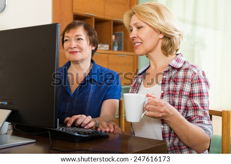 Two aged colleagues working on computer and smiling with cup of tea in hands - stock photo