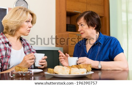 Two aged woman with cup of tea discussing something at home - stock photo