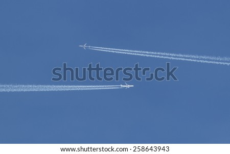 two aircraft on a collision course in a clear blue sky - stock photo