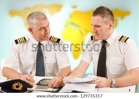 Two airline pilots preparing to flight, checking papers flight plan, log book. Pilots are sitting in AIS ARO Air Traffic Services Reporting Office - stock photo