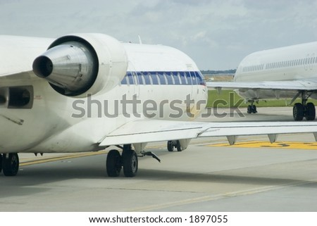 Two airplanes taxiing across a busy airport - stock photo