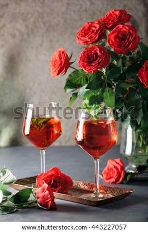 Two alcohol cocktails set with red roses. Romantic evening, valentine day celebration, chillout and party concept - stock photo