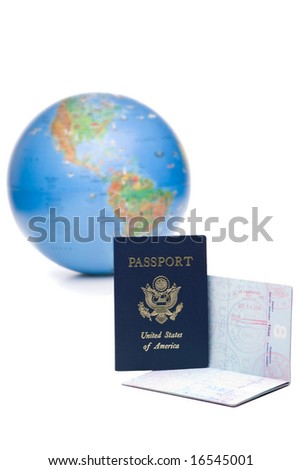 Two american passports stamped with travel visas, in front of out of focus world globe, on white background - stock photo