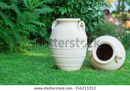 two amphorae on the green grass - stock photo