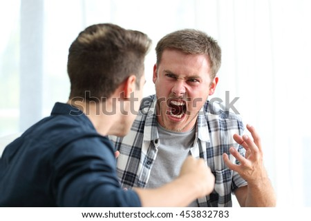 Two angry friends or roommates arguing and threatening in the living room at home - stock photo