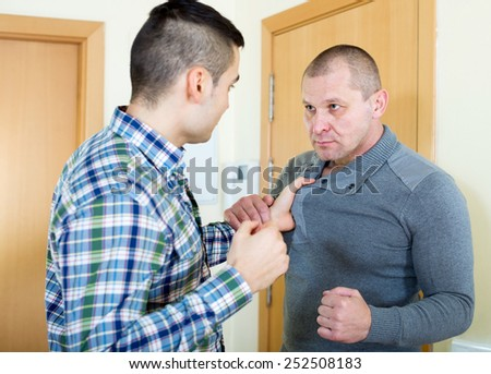 Two angry men looking at each other with clenching fists - stock photo