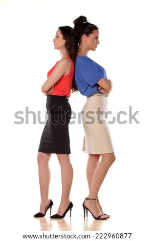Two angry women leans backs on each other - stock photo