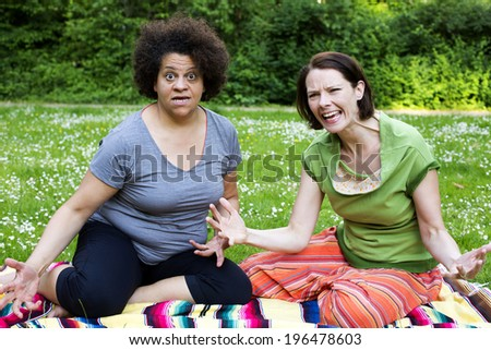 two angry women sitting on blanket in park - stock photo