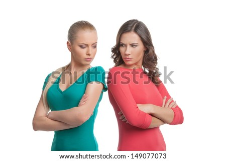 Two angry women. Two angry women looking at each other over shoulder and holding their arms crossed while isolated on white - stock photo