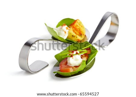 Two appetizer spoons garnished with basil tomato, potato and curd - stock photo