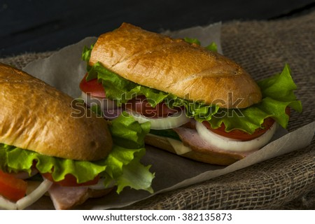 Two appetizing sandwiches with ham and vegetable slices on napkin. Fast food - stock photo