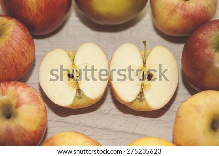 two apple halves in the middle surrounded by red and yellow apples. closeup, selective focus - stock photo