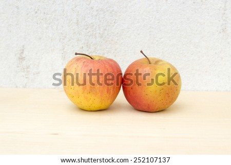 two apple still life on concrete wall and plywood background - stock photo