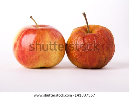 Two apples, young and old as a metaphor for aging. On a white background. - stock photo