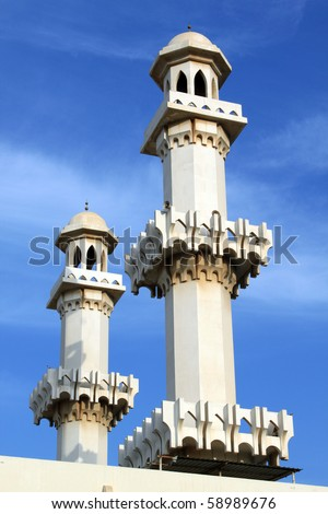 Two arabic minarets and blue sky in Bahrein - stock photo
