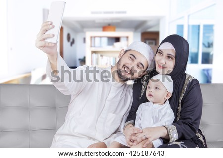 Two Arabic parents and their son sitting on the sofa while taking selfie picture together at home - stock photo