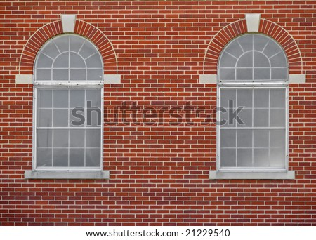 two arched windows on red brick building - stock photo