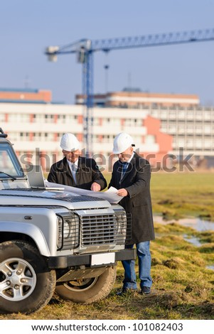 Two architect developers reviewing building plans at construction site - stock photo