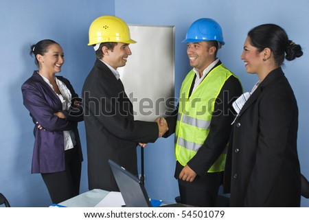 Two architect men's giving  hand shakes and  engineer woman laughing together and having fun - stock photo