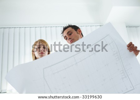 two architects examining blueprint indoors. Low angle view. Copy space - stock photo