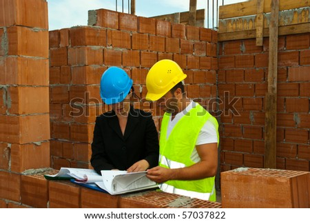 Two architects having a discussion and reading folders or looking on projects in a house under construction outdoor - stock photo