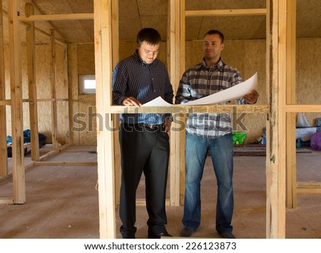 Two architects or builders consulting plans in a half built timber frame house - stock photo