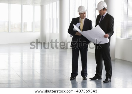 Two architects wearing hard hats looking at plans - stock photo