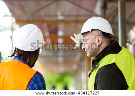 Two architects wearing hardhat and safety jacket pointing at scaffolding on construction site - stock photo