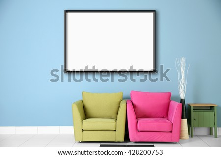Two armchairs and empty picture frame on blue wall background - stock photo