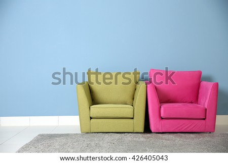 Two armchairs on blue wall background - stock photo