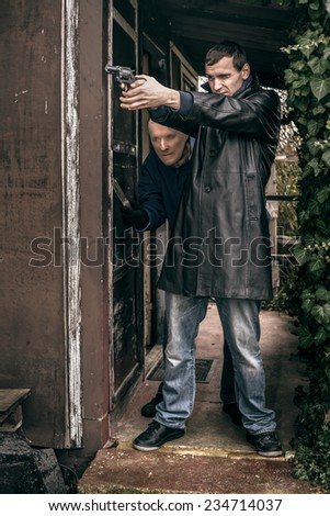Two armed men standing on the porch of old cabin. - stock photo