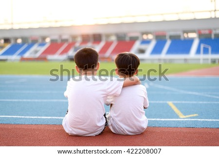 Two asian boy sit beside the blue running track and look to the stadium and sunset. - stock photo