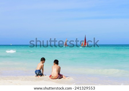 Two Asian boys playing on the white sandy beach in Cayo Santa Maria Cuba, rear view - stock photo