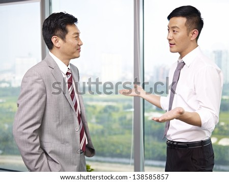 two asian business executives standing and talking by the windows in office. - stock photo
