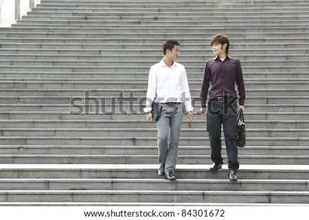 Two Asian Business men walking on stairs - stock photo