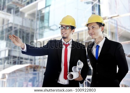 Two Asian businessmen with blueprint at construction site - stock photo
