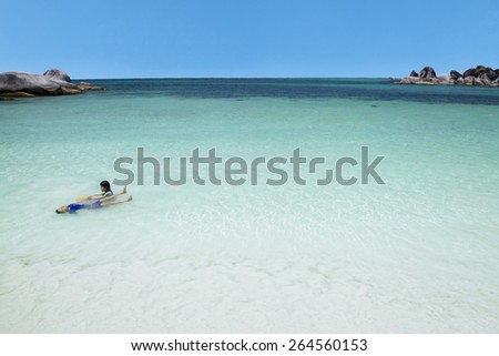 Two asian children playing and swimming together on the beautiful  beach - stock photo