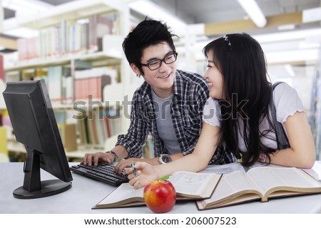 Two asian college students studying together at library - stock photo