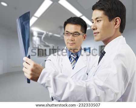 two asian doctors looking at x-ray film. - stock photo