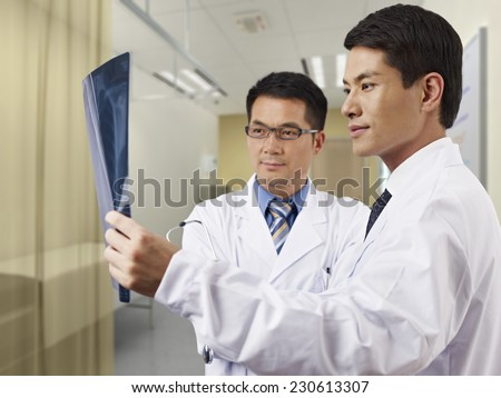two asian doctors looking at x-ray film in consultation room. - stock photo