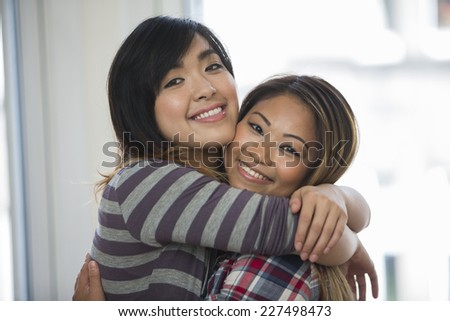 Two Asian female friends in sitting room at home, looking at camera  - stock photo