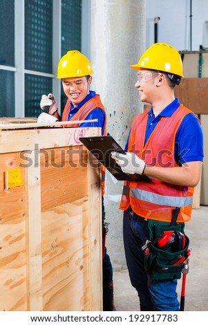 Two Asian Indonesian industrial or construction workers controlling with a checklist a delivery on a tower building site and open a wood box or cargo container with a crowbar  - stock photo