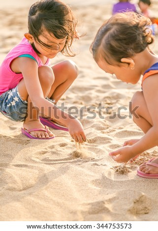 Two Asian Little Girl Enjoy Playing on The White  Beach Sand, Selective Focus on Hand - stock photo