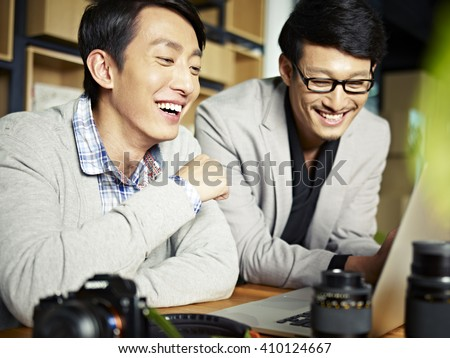 two asian photographers working together selecting images using laptop computer, happy and laughing. - stock photo