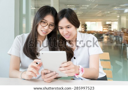 Two Asian student with uniform in classroom with electronic tablet - stock photo
