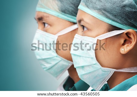 Two Asian surgeon in close up looking away to empty space - stock photo