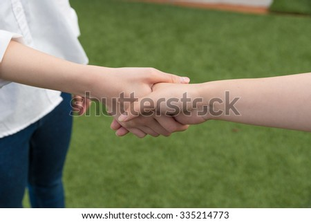 two asian woman shaking hands - stock photo