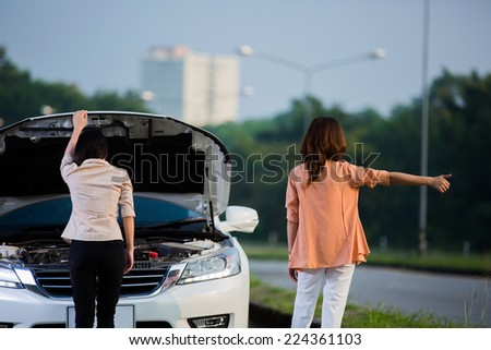 Two Asian women are doing a breakdown on the road stance to the car park - stock photo