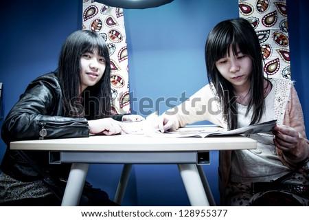 two Asian women reading  magazine - stock photo