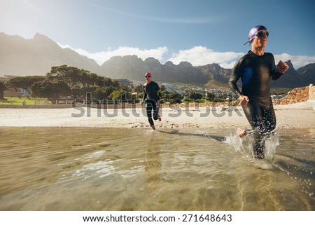 Two athletes training for a triathlon. Triathlon participants running in the water. - stock photo